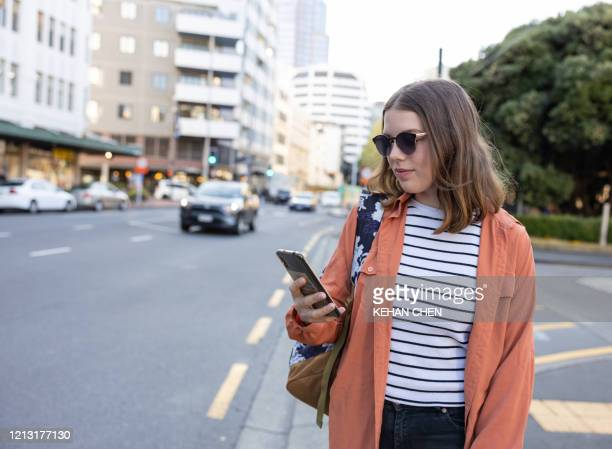 young woman using mobile app on smart phone to arrange taxi ride in downtown city street - クラウドソーシング ストックフォトと画像