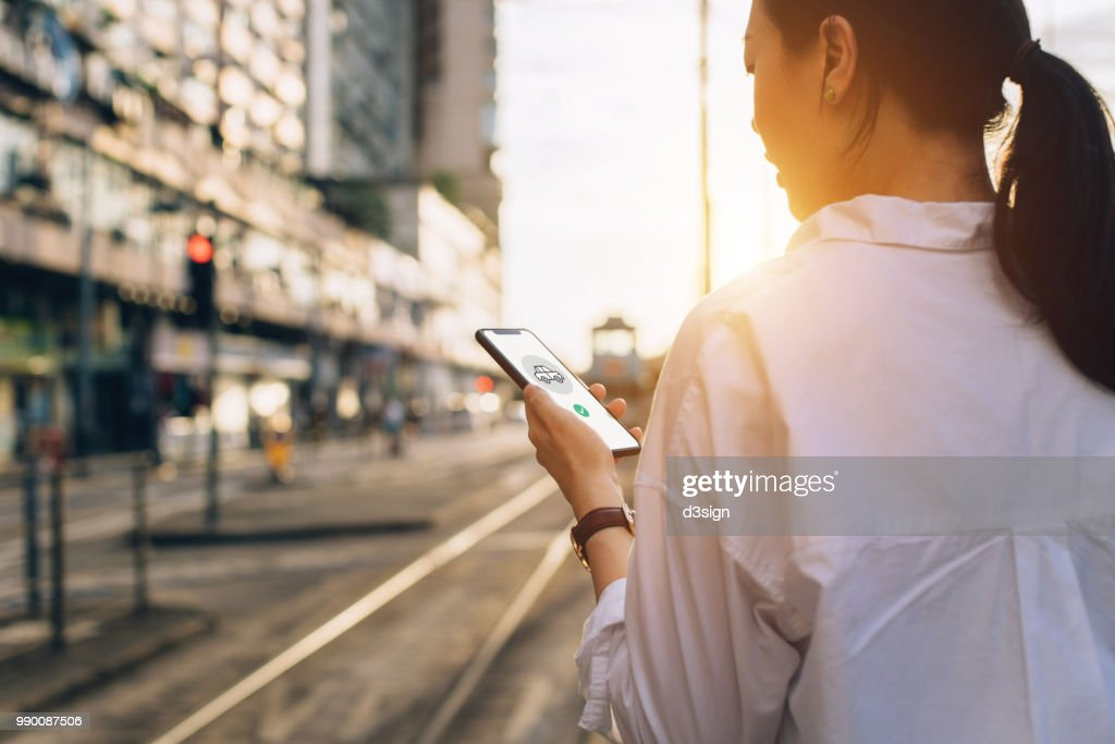 Young woman using mobile app on smartphone to arrange transportation ride in city street at sunset : Stock Photo