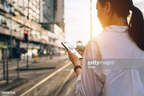 young woman using mobile app on smartphone to arrange transportation ride in city street at sunset - mobiles gerät stock-fotos und bilder