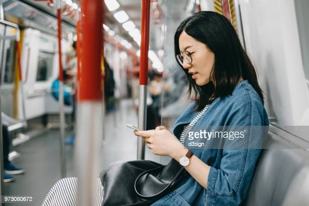 young woman using mobile app while riding in the subway - public transport stock pictures, royalty-free photos & images