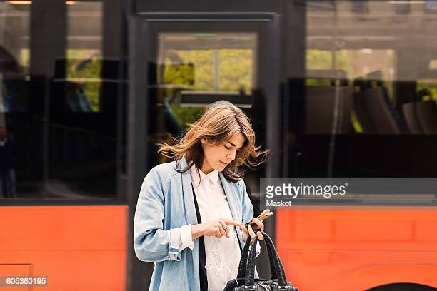 Young woman using mobile phone against bus