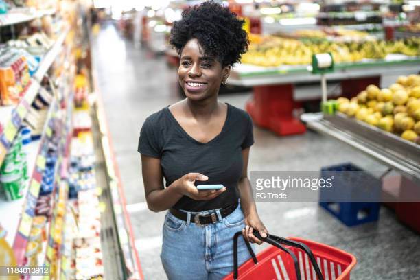 young woman using mobile phone and choosing product in supermarket - groceries stock pictures, royalty-free photos & images