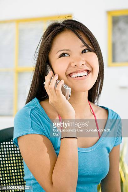 """young woman using mobile phone and smiling - """"compassionate eye"""" stock pictures, royalty-free photos & images"""