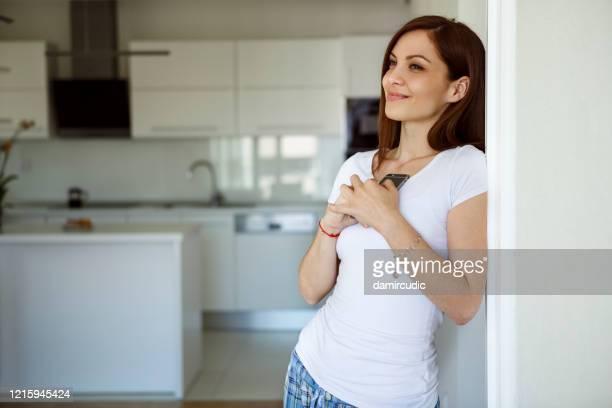 young woman using mobile phone at home - sonhar acordado imagens e fotografias de stock