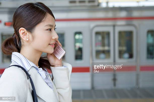Young woman using mobile phone at platform, smiling