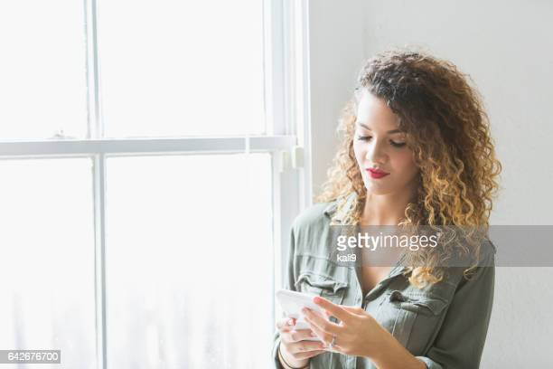 Young woman using mobile phone by sunny window