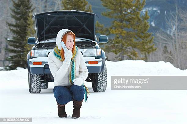 Young woman using mobile phone crouching by broken down car