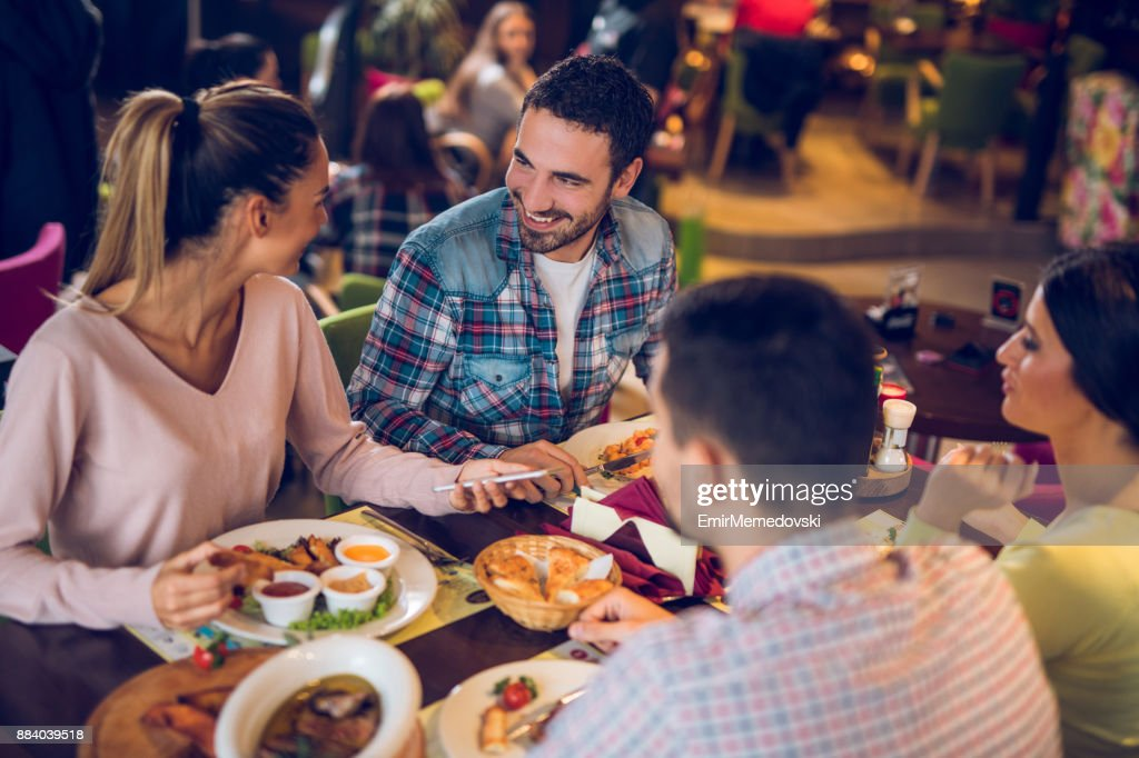 Young woman using mobile phone during lunch with friends : Stock Photo