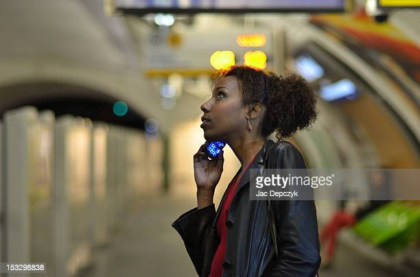young woman using mobile phone in a metro station - depczyk stock pictures, royalty-free photos & images
