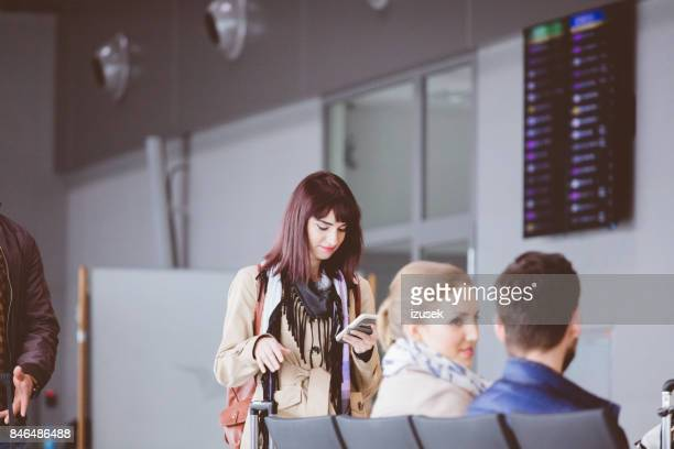 Young woman using mobile phone in airport terminal