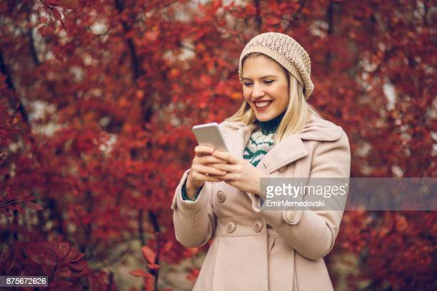 young woman using mobile phone in an autumn park - emir memedovski stock pictures, royalty-free photos & images