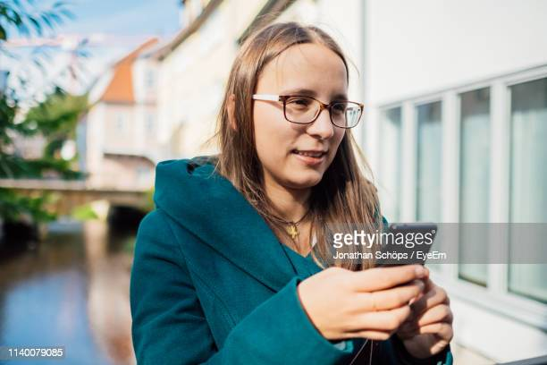 young woman using mobile phone in city - erfurt stock-fotos und bilder