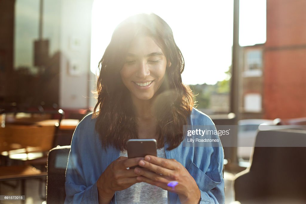 Young woman using mobile phone in coffee shop : Foto de stock