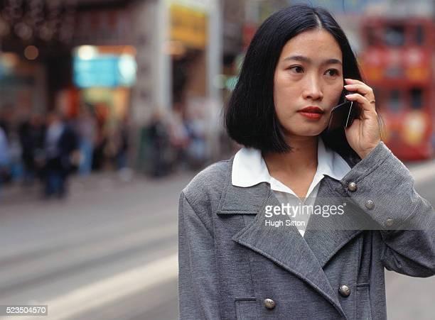 young woman using mobile phone in street, hongkong, china - hugh sitton stock-fotos und bilder
