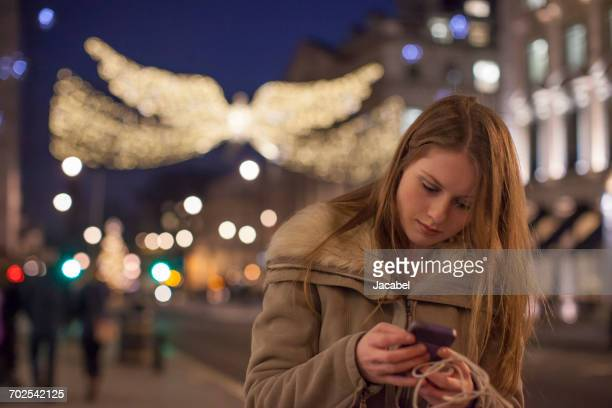 Young woman using mobile phone in street, London, UK
