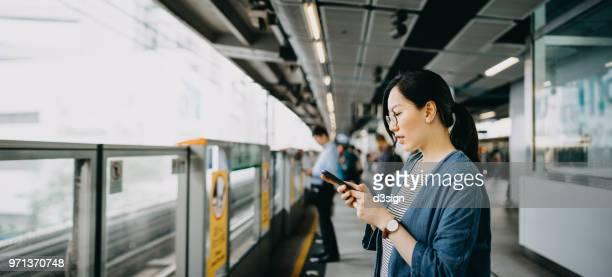 young woman using mobile phone in subway station platform - stazione della metropolitana foto e immagini stock