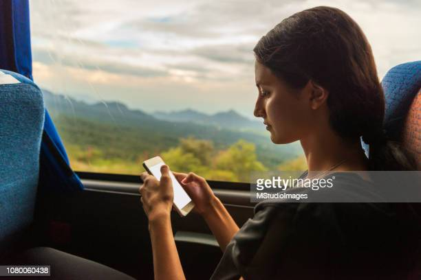 young woman using mobile phone in the bus. - bus stock pictures, royalty-free photos & images