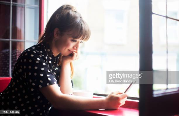 Young woman using mobile phone in window