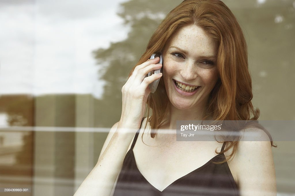 Young woman using mobile phone, laughing, view through window : Stock Photo