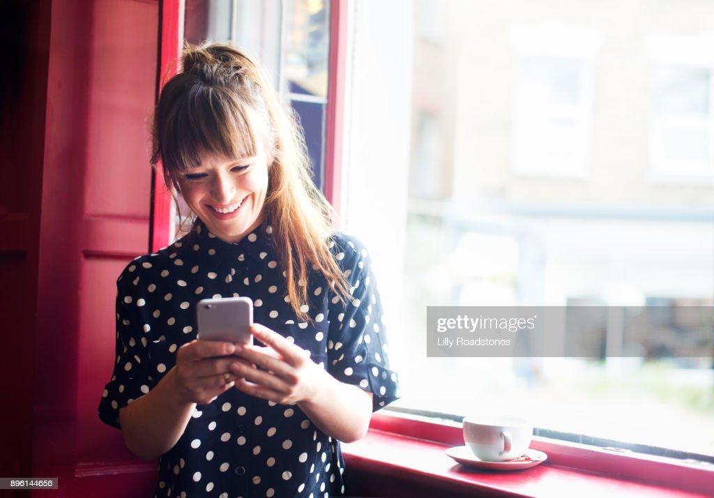 Young woman using mobile phone near window : Foto de stock