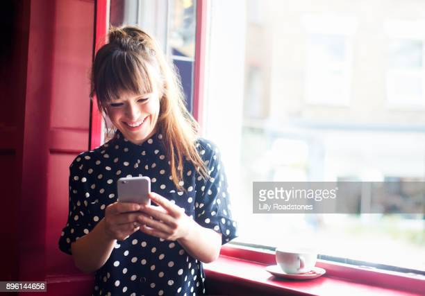 young woman using mobile phone near window - one young woman only stock pictures, royalty-free photos & images