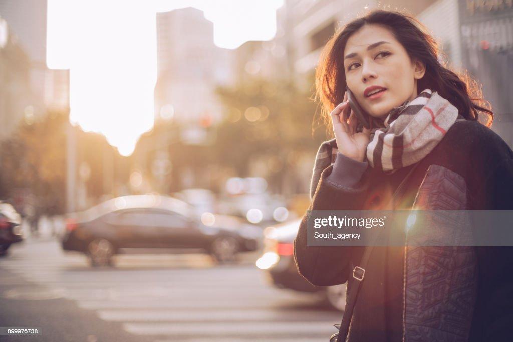 若い女性が路上で携帯電話を使用して : ストックフォト