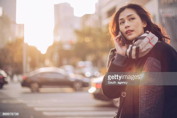 Young woman using mobile phone on the street