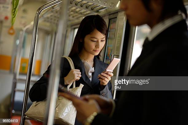 Young woman using mobile phone on the train