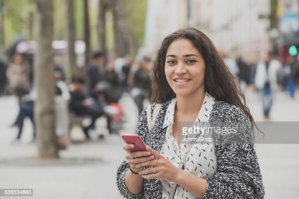 Jeune femme à l'aide d'un téléphone mobile et souriant