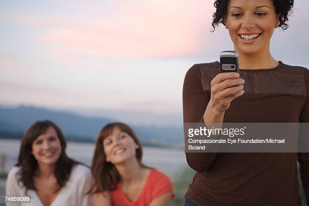Young woman using mobile phone, two sitting in background, smiling
