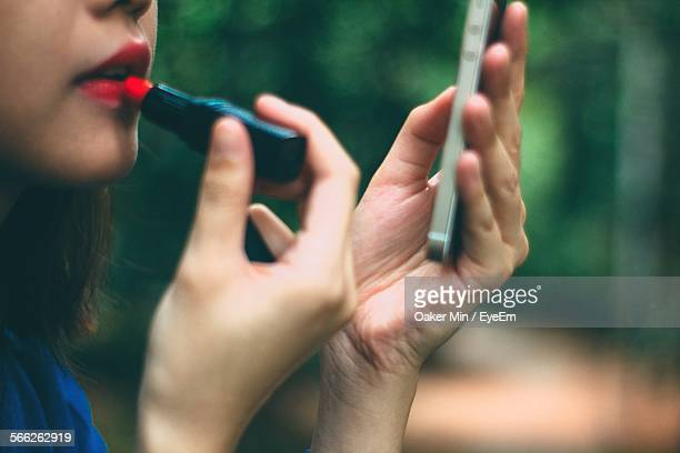 Young Woman Using Mobile Phone While Applying Lipstick