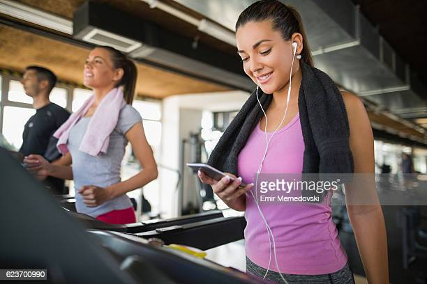 Young woman using mobile phone while exercising on treadmill.