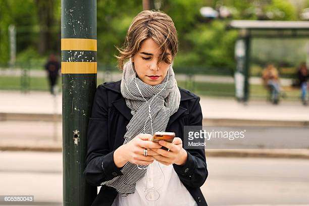 Young woman using mobile phone while listening to music through headphones at tram station