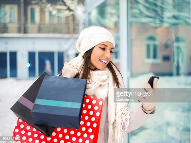 Young woman using mobile phone while shopping