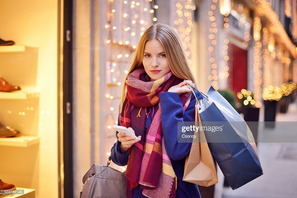 Young woman using mobile phone while shopping : Stock Photo