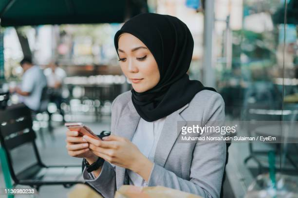 young woman using mobile phone while sitting at cafe - surfing the net stock pictures, royalty-free photos & images