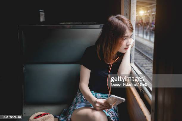 Young Woman Using Mobile Phone While Sitting In Train