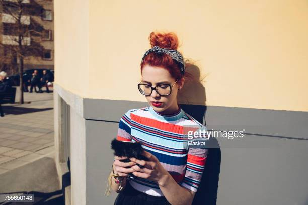 young woman using mobile phone while standing against wall - phone cover stock pictures, royalty-free photos & images