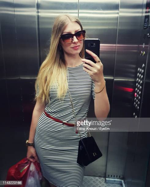 young woman using mobile phone while standing in elevator - elena knouzi stock pictures, royalty-free photos & images