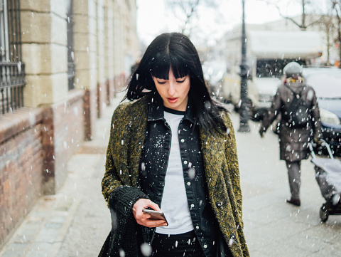 Young Woman Using Mobile Phone While Standing On Street While Snowing - gettyimageskorea