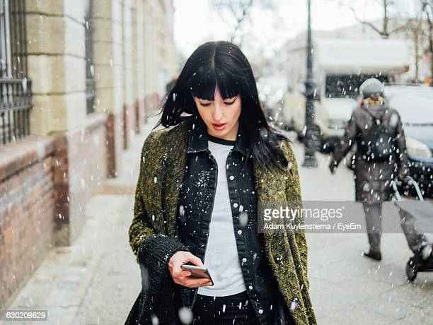 young woman using mobile phone while standing on street while snowing - kälte stock-fotos und bilder
