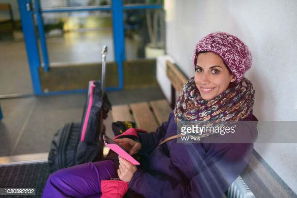 Young woman using mobile phone while waiting for the bus in Kemi Station Lapland