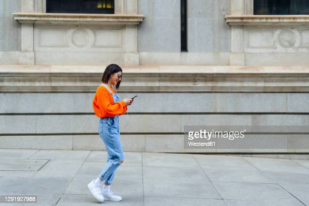young woman using mobile phone while walking against wall on footpath - bib overalls stock pictures, royalty-free photos & images