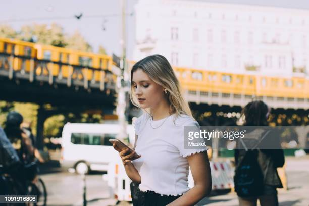 young woman using mobile phone while walking by street in city - städtische straße stock-fotos und bilder