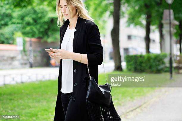 Young woman using mobile phone while walking on footpath at park