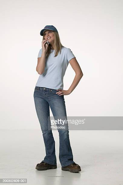 Young woman using mobile phone with hand on hip, posing in studio, portrait