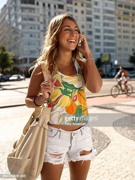 young woman using mobile phone with handbag, smiling - copacabana beach stock pictures, royalty-free photos & images