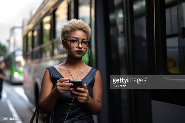 jovem mulher usando mobile espera o ônibus - waiting - fotografias e filmes do acervo