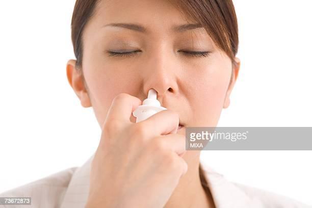 A young woman using nasal spray