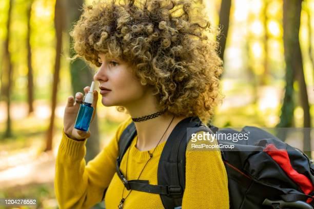 jovem usando spray de nariz para alergia ao ar livre - gota condição médica - fotografias e filmes do acervo